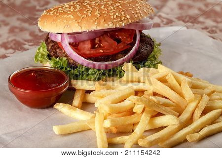 Fresh hamburger with French fries and tomato sauce. Close-up