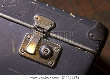 Folding latch on the lock of an old shabby suitcase