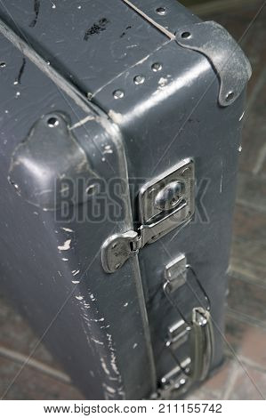 Old shabby suitcase on latches on a wooden floor toning