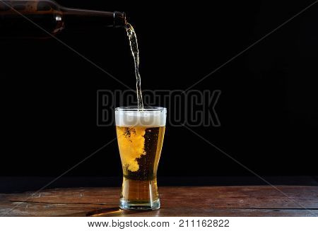 Pouring Beer In A Glass On A Wooden Table, Dark Background