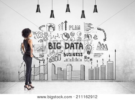 Portrait of a strong and independent African American woman wearing black and standing with her hands on the waist. Concrete wall with a big data sketch