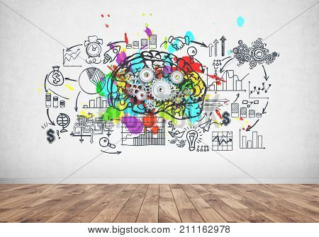 Large and colorful brain with gears on it is drawn on a concrete wall with a business plan sketch. Concept of strategy and creativity in business.