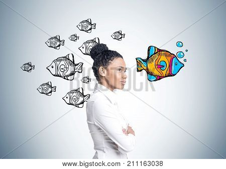 Portrait of a strong and independent African American woman wearing a white shirt and standing with crossed arms near a concrete wall with fish swimming in another direction