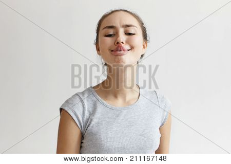 Horizontal shot of funny humorous playful young European woman in grey t-shirt sticking out her tongue trying to touch nose with its tip. People youth leisure joy fun and entertainment concept