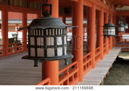 Miyajima - Japan, May 26, 2017: Black lanterns and red pillars at the famous the Itsukushima Shrine on Miyajima