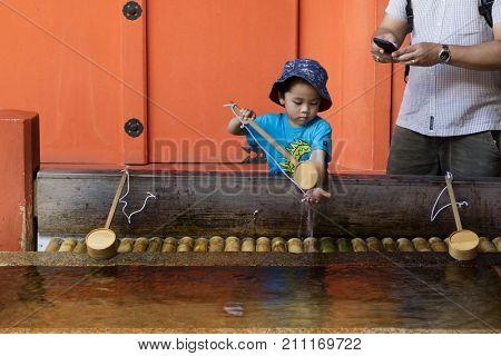 Miyajima - Japan, May 26, 2017: Child is cleaning hands at a purification fountain of the famous the Itsukushima Shrine on Miyajima