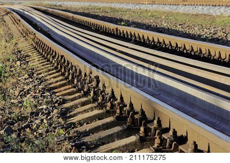 Several rails lie on the sleepers between the main rails on the railway. bolts that secure the rails to the sleepers on the railway direction.