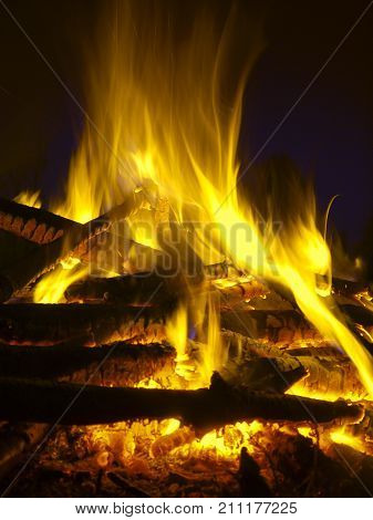 Fire flames of a bonfire on a black background. Bright hot campfire burning at night. Large pile ignited. Balefire or blaze is for hiking pagan and ancient traditions natural lifestyle devil etc