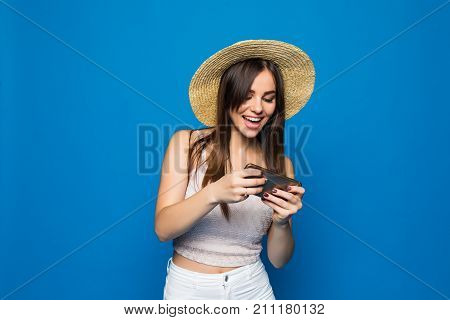 Woman Play Game On Her Cell Phone Isolated Over Blue Background