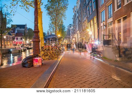 AMSTERDAM HOLLAND - AUGUST 172017; lights on street and canal in long exposure night scene people blurred in motion and bicycles that abound in this city.