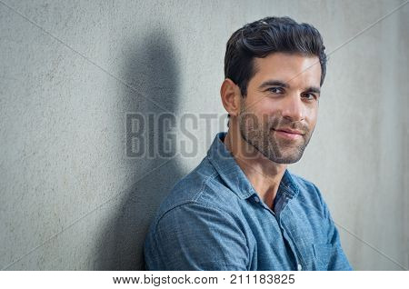 Handsome young man posing on grey background. Portrait of satisfied businessman against grey wall. Close up face of fashionable latin man on grey background. poster
