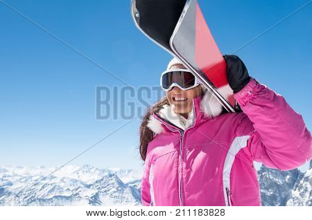 Sporty woman carrying ski on shoulder and looking snowy mountain. Smiling girl carrying a pair of red skis with copy space. Beautiful skier woman ready to ski in winter vacation.