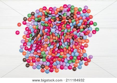 Close up of a pile of colorful chocolate coated candy on a white wooden table. Chocolate pattern. Chocolate background