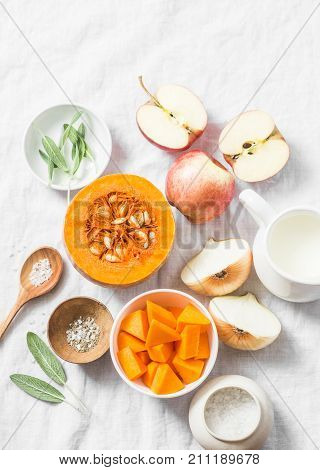 Ingredients for pumpkin apple soup on white background top view. Pumpkin apples cream onion sage - ingredients for a healthy lunch