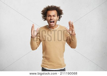 Emotional Angry Afro American Male Shouts Loudly At Someone In Despair And Aggression, Being Fed Up
