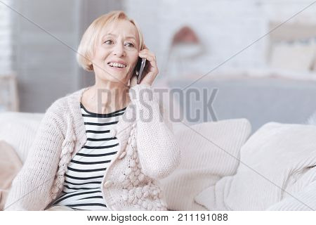 So happy to hear you. Excited elderly woman sitting on a sofa and grinning broadly while having a pleasant smartphone conversation indoors.