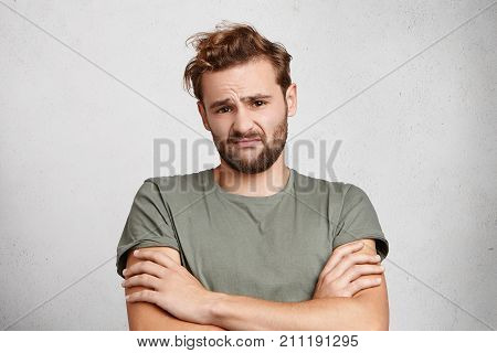 Displeased man with beard and mustache frowns face expresses hesitation and concern crosses hands dressed casually. Unsatisfied male looks tired after long sleepless night and work on project poster