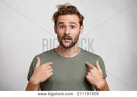 Portrait Of Handsome Bearded Young Man Points At Himself Being Puzzled To Be Chosen. Astonished Attr