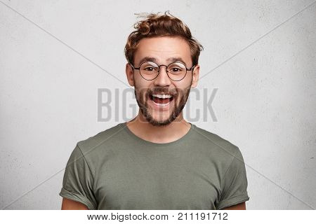Funny Smiling Unshaven Male Wonk Wears Round Spectacles And Casual Clothes, Being Glad To Recieve In