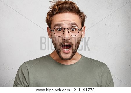 Indoor Shot Of Surprised European Man Opens Mouth Widely, Being Shocked To Hear Horrified News, Isol