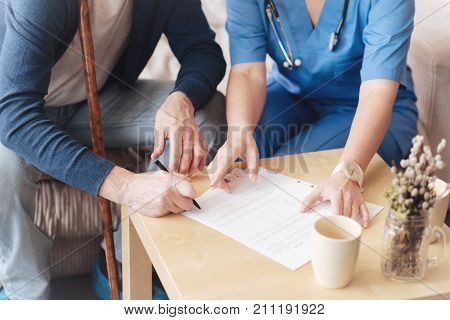 Patient form. Close up look on a female medical worker pointing toward a paper while helping her elderly male patient to fill all the blanks of a health insurance application indoors.