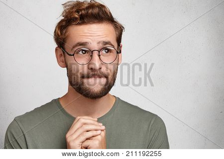 Indoor Shot Of Pleasant Looking Man Keeps Palms Together, Has Hopeful Inspired Look, Asks For Good L
