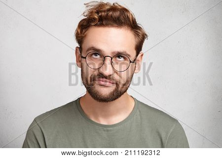 Portrait Of Stylish Bearded Man With Bored Fed Up Expression, Looks Displeased Up, Being Tired To Ex