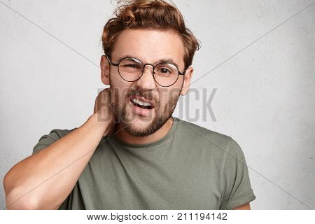 Tired Male Freelancer Works Remotely, Rubs Neck, Feels Pain After Long Hours Spending Near Computer