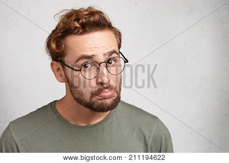Offended Upset Young Stylish Male Curves Lower Lip Has Grumpy Expression, Poses Against White Backgr
