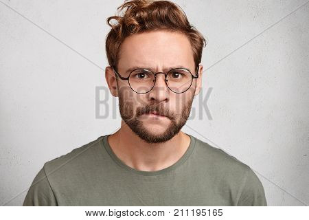 Puzzled Serious Irritated Angry Young Unshaven Man With Beard And Mustache Curves Lips, Has Sullen E