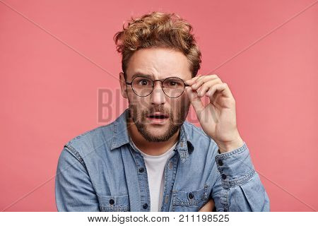 Scrupulous Stylish Man In Denim Shirt And Spectacles Looks With Shocked And Stupefied Expression, Tr
