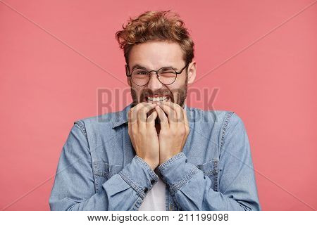 Portrait Of Joyful Handsome Bearded Hipster Guy Clenches Teeth, Blinks Eye, Bites Nails, Waits To He