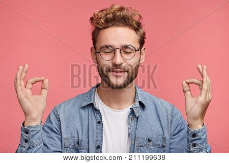 Relaxed Carefree Male Student Meditates Against Pink Background, Tries To Relax After Long Hours Of