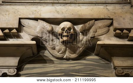 Marble skull and wings on the wall in the Catholic church in Rome Italy.