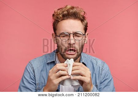 Portrait Of Ill Or Sick Bearded Male Sneezes And Coughs, Uses Handkerchief, Rubs Nose, Being Allergi