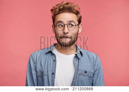 Good Looking Male Model With Stubble Presses Lips, Looks Pensively Aside, Thinks Over His Future Act