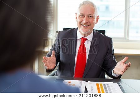 Portrait of friendly senior Caucasian consultant sitting at table, talking to female client or partner and smiling in office. Meeting and relationship management concept