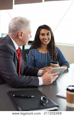Cheerful Hispanic intern learning from mentor and looking at camera in board room. Happy young business lady discussing project with boss at meeting. Teamwork concept