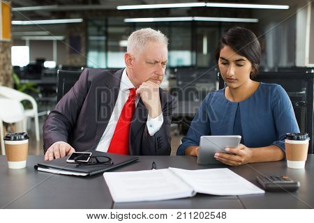 Concentrated boss and secretary reviewing report on tablet and elaborating business strategy. Serious business colleagues monitoring stock market on internet. Technology concept