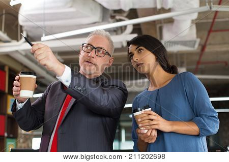 Confident architect explaining project to coworker at construction site. Successful senior businessman pointing with pen and describing plan of room. Colleagues drinking coffee. Business in factory concept