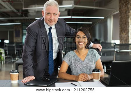 Confident senior boss working with ambitious intern and supporting her ideas. Successful business colleagues working together in office. Boss and assistant concept