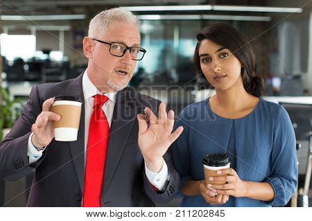 Enterprising boss with coffee brainstorming with young colleague while working on project. Confident multiethnic business partners looking at camera like it is whiteboard. Planning business concept