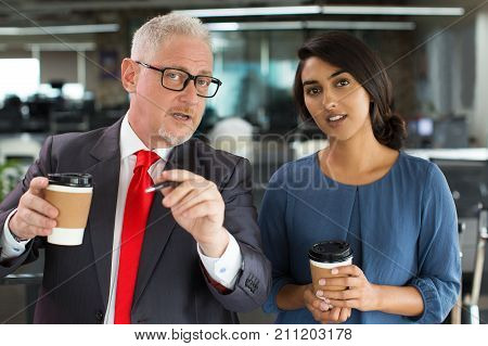Intelligent boss presenting his strategy to assistant and pointing at camera. Confident senior businessman explaining his plan of further work. Teamwork concept