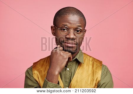 Horizontal Portrait Of Handsome Male Adult Has Dark Skin, Keeps Hand Under Chin, Looks Confidently,