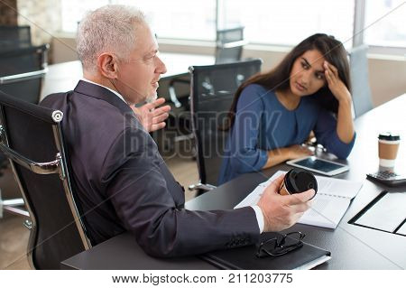 Senior boss offering new strategy of business development. Confident executive presenting his idea at staff meeting and giving arguments. Exhausted business meeting concept