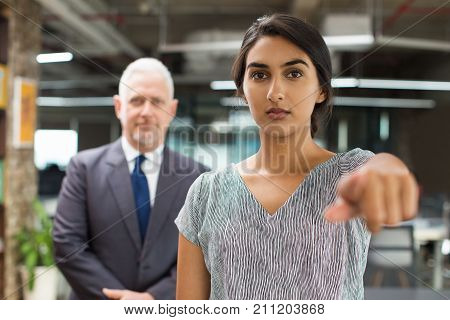 Serious business lady pointing to camera in office. Confident young Hispanic human resources manager finding new job applicant. Choice concept