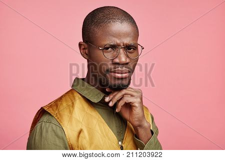 Indoor Shot Of Strict African Male Boss, Dressed Formally, Wears Glasses, Looks In Discontent Expres