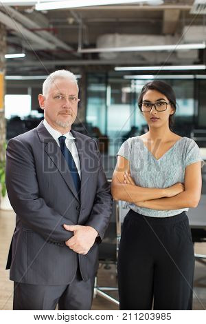 Serious confident executive and his secretary in formalwear looking at camera in office. Senior boss wearing suit and business lady in eyeglasses standing in office. Company concept