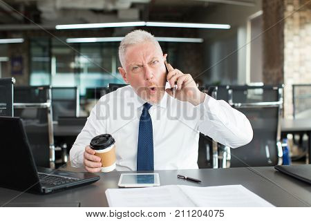 Shocked emotional businessman talking on phone and looking at camera. Astonished handsome senior executive receiving breaking news. Excited manager concept