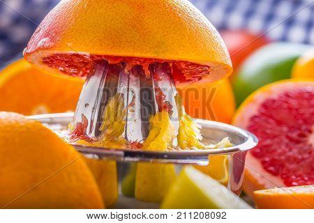 Preparation Of Orange Grape Or Multivitamin Juice, Hands Squeeze Juice On A Manual Metal Juicer Surr